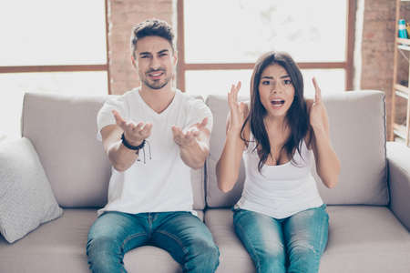 Upset young couple is frustrated about the loss of the team in game they are watching. They are fans of sports games as football, basketball, hockey, baseball Stock Photo