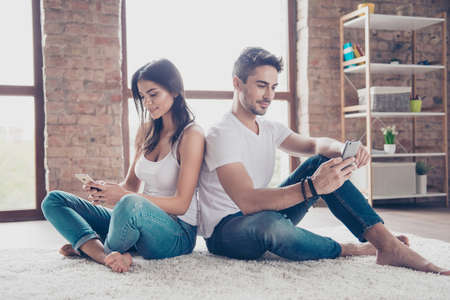 Beautiful relaxed brother and sister are browsing on their phones, sitting on the floor on comfortable carpet at home. They are in casual outfit, so calm and focused