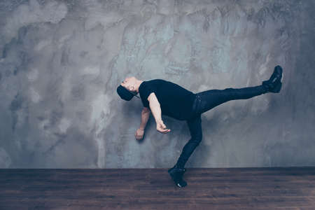 down beat: Freedom! A guy is doing a dance move which looks like he is going to float in the air. Dancer is in the black outfit and cap, relaxed Stock Photo