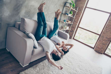 Go crazy together! Relaxing upside down is fun. Cheerful brother and sister are lying on the beige sofa at home indoors, in jeans and white casual t shirts