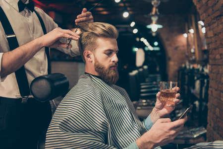 Entspannen Sie im Friseurladen. Seitenansicht des hübschen jungen roten bärtigen Mannes, der Scotch trinkt und an seinem pda grast, beim Erhalten eines Haarschnitts