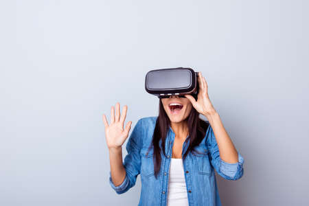 Wow! Excited latinn girl in a VR glasses surprised with what she saw. She is touchinmg sonmething and express the emotions from this experience