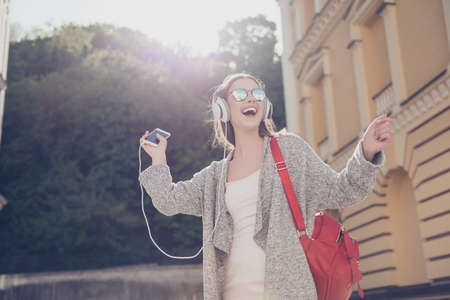 Carefree girl is listening to favourite song and dancing outside, wearing cozy outfit and sunglasses, red backpack