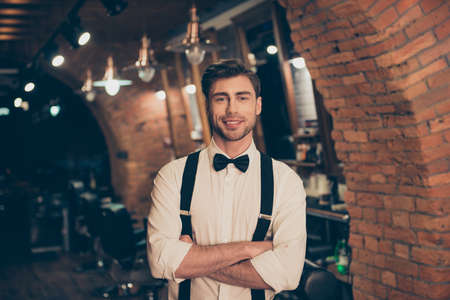 hair stylist: Attractive young brunette bearded guy in a barber shop, standing with crossed hands, smiling, dressed classy and retro style
