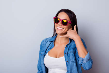 Cheerful latin girl with beaming smile is gesturing to call her with a hand. She is wearing casual jeans shirt and white singlet, sunglasses and stands on a light background
