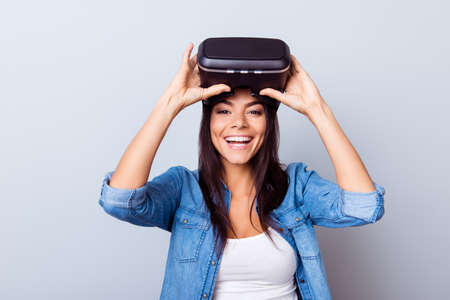 Cheerful hispanic girl is taking off  VR glasses and smiles widely, new experience is so cool! Banco de Imagens