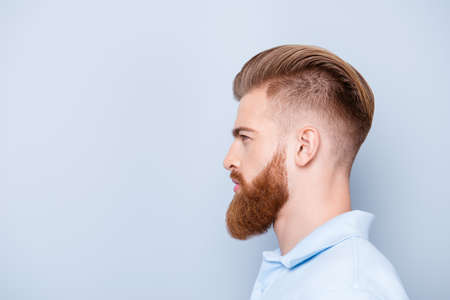 Advertising barbershop concept. Profile side portrait of confident handsome red bearded young man. He has a perfect stunning hairstyle, modern haircut