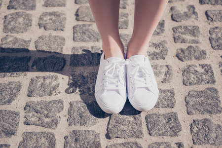 Cropped close up photo shot of a girl`s legs in white gumshoes on the cobbles. She is on vacation, having fun. Sunny day
