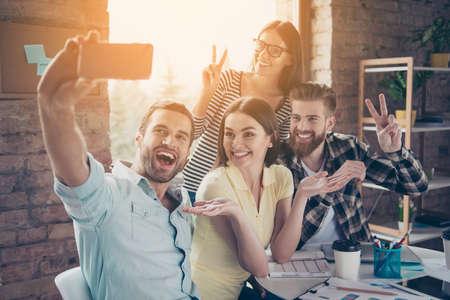 Emocionados jóvenes felices haciendo selfie en la cámara del teléfono inteligente siendo muy positivo y relajado. Muestran asombro, felicidad, signo de dos dedos Foto de archivo - 82694593