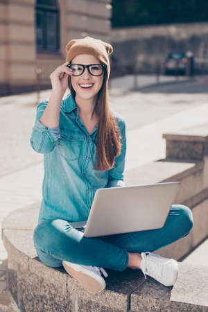Excited attractive girl is doing her university project on a laptop outside on a sunny day. She is wearing casual clothes, glasses and a hat