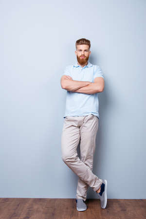 Success concept. Confident handsome red bearded young man in casual stylish outfit, standing on the pure background, his hands and legs are crossed Stock Photo