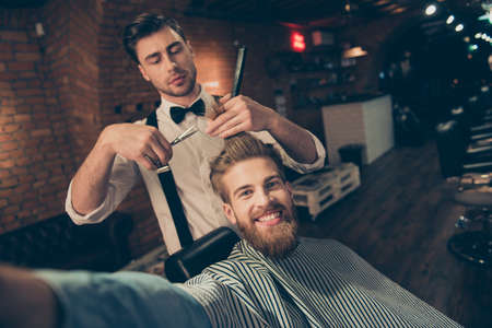 Cheerful handsome stylish red bearded guy with beaming smile is taking selfie at barber shop, stylish is making him a brand new haircut
