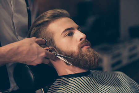 Close up of a hairdresser`s work for an attractive young man at the barber shop. He is doing styling of a red beard with scissors