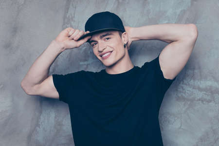 Close up portrait of young cute guy in cap, which is standing on the grey background. He is in black t shirt and jeans, smiling and holding his head and cap