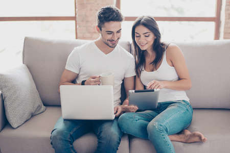 So easy! Excited beautiful happy couple is doing online shopping in internet. They are indoors at home on cozy couch in casual clothes, relaxing and buying goods easily 免版税图像