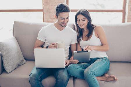 So einfach! Aufgeregtes schönes glückliches Paar tut Onlineeinkaufen im Internet. Sie sind zuhause auf einer gemütlichen Couch in legerer Kleidung zu Hause, entspannen sich und kaufen leicht Waren