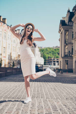Cheerful dreamy girl jumping, posing for photo on vacation. She is so carefree, wearing hat, sunglasses, pure light dress