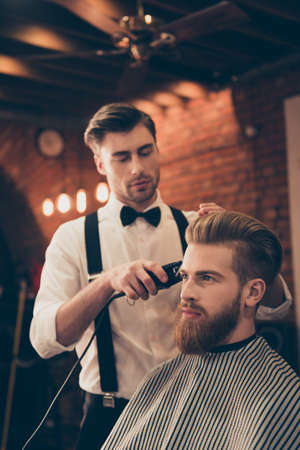 hair stylist: Beard styling for a handsome young guy at the barber shop. Hairdresser is attractive and wearing classic outfit, he is focused and serious
