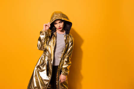 Fashionable girl is in shining gold coat with a hood on the yellow background. She looks so impressing and harsh