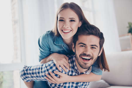 Beautiful couple of young lovers are hugging indoors at home, looking at the camera, wearing casual clothes Stok Fotoğraf - 82768908