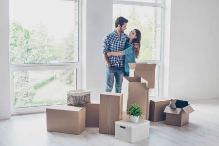 Successful young couple is moving to new nice place and embracing, around are carton boxes with their belongings. The room is very light and bright, they are wearing casual outfit Stok Fotoğraf