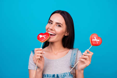 beaming: Charming young brunette with red candies hearts on bright blue background in casual outfit. So girlish!