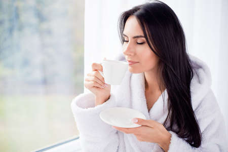 Close up portrait of charming dreamy brunette young girl drinking coffee. She is sleepy and relaxed