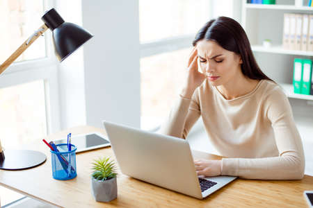 Young beautiful woman is sitting at the desk in the office, she is tired, she has a headache Stockfoto