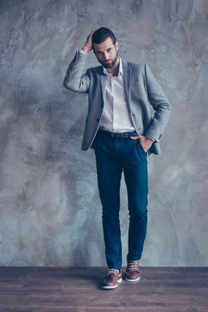 コンクリートの灰色の背景の上に立って、上品な若いひげを生やしたビジネス人の完全な長さの肖像画。彼は素晴らしいですね。彼の髪型を固定の