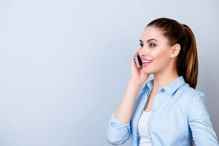 Pretty young smiling woman in blue shirt talking on mobile phone against gray background Banco de Imagens - 82769342