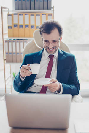 Close up portrait of successful businessman broker, who is resting at his office. He did a great job, so is satisfied and taking pause to relax with coffee and laughing