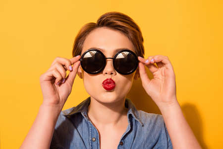 Fashionable young cute girl in trendy sunglasses sends a kiss against bright yellow background, she holds spectacles with her hands