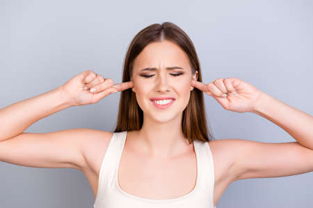 Portrait of tired young cute girl, closing her ears with fingers. She is with closed eyes also, in a white casual singlet on pure background Stock Photo