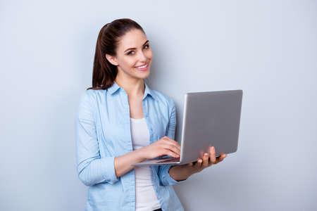 Jonge gelukkige glimlachende vrouw die in vrijetijdskleding laptop houdt en e-mail naar haar beste vriend verzendt