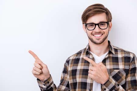 Estudiante exitoso en una camisa a cuadros marrón y gafas con cerdas muestra el espacio de copia sobre fondo blanco puro Foto de archivo