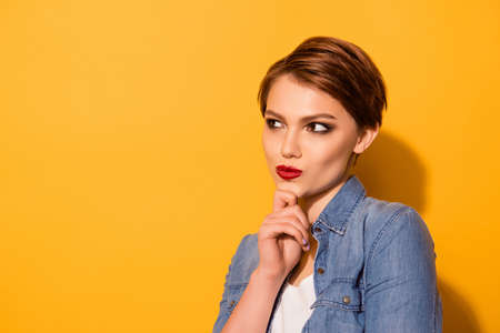 Close up portrait of minded attractive young lady with red lipd dressed in jeans shirt thinking about what to choose