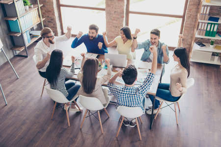 Top view of team of business partners with raised up hands in light modern workstation, celebrating the growth of their company