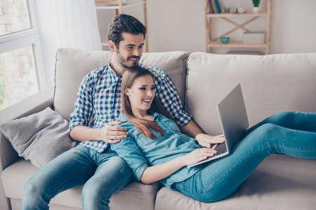 興奮して美しい幸せなカップルは、インターネットでオンライン ショッピングをやっています。彼らは、カジュアルな服を着て、リラックスして簡 写真素材