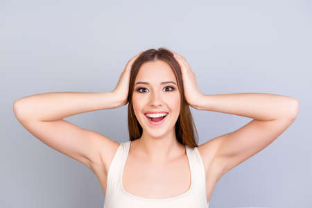 Young carefree dreamy cute girl in white casual singlet on pure light background. She is shocked, holding her head
