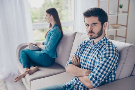 Annoyed couple is ignoring each other, sitting on the couch indoors at home with sad faces