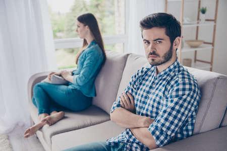 Pareja molesta se está ignorando, sentada en el sofá en el interior en su casa con caras tristes Foto de archivo - 82770262