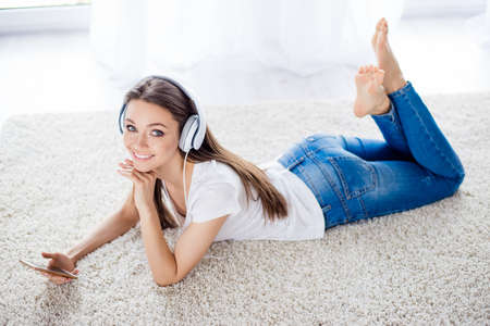 Pretty young lady is listening to the music with headphones at home lying on the white carpet