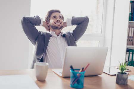 꿈꾸는 젊은 수염 된 기업가 그의 워크 스테이션에서 노트북 앞에 쉬고있다. 그는 행복하고 미소를 지으며 위를보고 있습니다.
