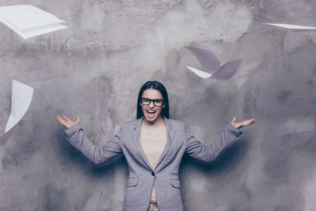 Angry woman in is screaming and tossing the papers on the grey background