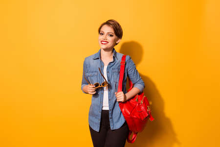Portrait of pretty young smiling female student dressed in jeans shirt with sunglasses in hand and red backpack on shoulder Stock Photo