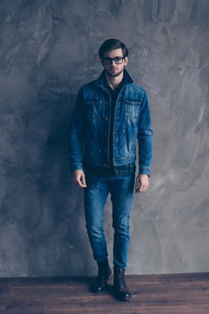 Young serious bearded guy in casual jeans outfit is standing on a concrete wall`s background, wearing glasses and look pensive