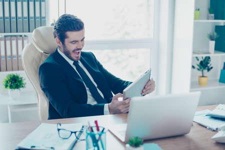 陽気な青年実業家がオフィスに彼のタブレットにゲームを通っています。彼は非常に興奮して、正装を着て 写真素材