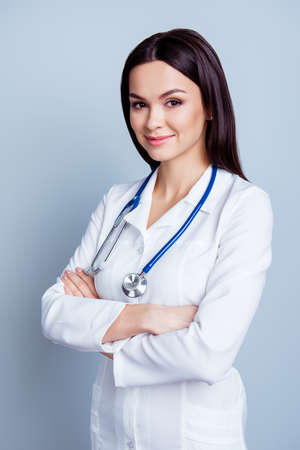 Vertical portrait of young confident female medico standing with crossed hands on gray backdrop