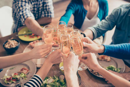 Cropped close up photo of glasses with champagne. Young people are toasting to celebrate the event. Table is full of tasty food and drinks