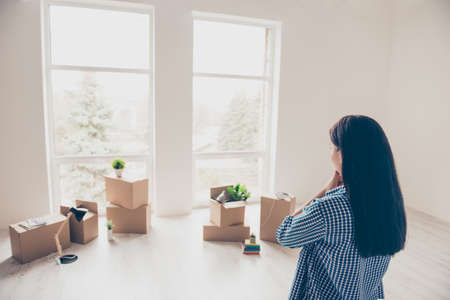 Dream come true! A start of new life! Brunette woman moved in to new light and modern apartment. She is looking at boxes with her belongings, planning how she will organize the space here Фото со стока